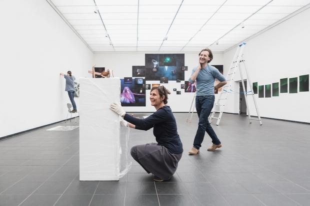 Foto: Menschen, die Bilder aufhängen